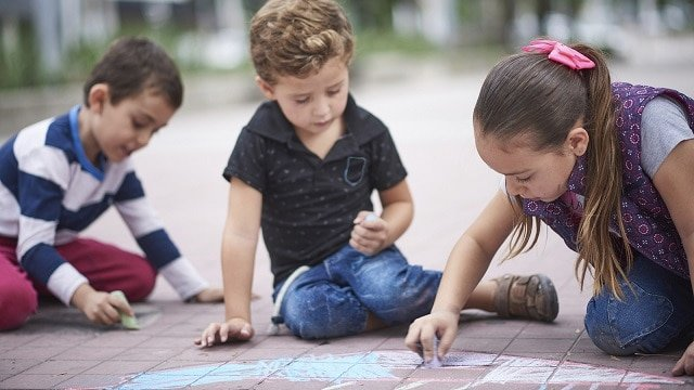 Hispanic boys and girl drawing with chalk on sidewalk